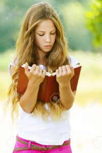 15282496-beautiful-teenage-girl-reading-red-book-against-green-of-summer-stock-photo